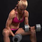 Αθλητική γυναίκα bodybuilder με τους αλτήρες όμορφο ξανθό κορίτσι με τους μυς Στοκ Φωτογραφία