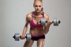 Αθλητική γυναίκα bodybuilder με τους αλτήρες όμορφο ξανθό κορίτσι με τους μυς Στοκ Εικόνα