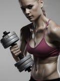 Αθλητική γυναίκα bodybuilder με τους αλτήρες όμορφο ξανθό κορίτσι με τους μυς Στοκ εικόνες με δικαίωμα ελεύθερης χρήσης
