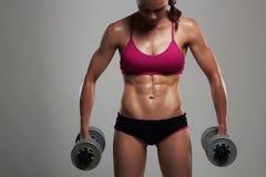 Αθλητική γυναίκα bodybuilder με τους αλτήρες όμορφο ξανθό κορίτσι με τους μυς Στοκ εικόνα με δικαίωμα ελεύθερης χρήσης
