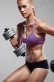 Αθλητική γυναίκα bodybuilder με τους αλτήρες όμορφο ξανθό κορίτσι με τους μυς Στοκ Εικόνες