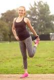 Αθλητική νέα γυναίκα που κάνει τις τεντώνοντας ασκήσεις Στοκ Εικόνα