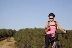 Αθλητική νέα γυναίκα σε ένα ποδήλατο βουνών Στοκ φωτογραφία με δικαίωμα ελεύθερης χρήσης