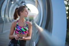Αθλητική νέα γυναίκα χρησιμοποιώντας το κινητό τηλέφωνό της και ακούοντας τη μουσική για την άσκηση Στοκ εικόνα με δικαίωμα ελεύθερης χρήσης