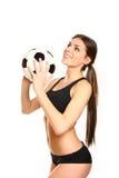 Αθλητική τοποθέτηση κοριτσιών με μια σφαίρα ποδοσφαίρου σε ένα άσπρο υπόβαθρο Στοκ Φωτογραφίες