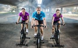 Αθλητικοί άνθρωποι που εκπαιδεύουν την οδήγηση ποδηλάτων στοκ εικόνες