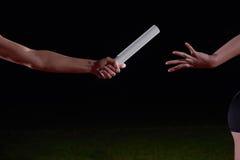 Αθλητικοί δρομείς που περνούν το μπαστούνι στη φυλή ηλεκτρονόμων Στοκ φωτογραφία με δικαίωμα ελεύθερης χρήσης