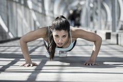 Αθλητικός αθλήτρια που κάνει την ώθηση επάνω πρίν τρέχει στην αστική κατάρτιση workout Στοκ φωτογραφία με δικαίωμα ελεύθερης χρήσης