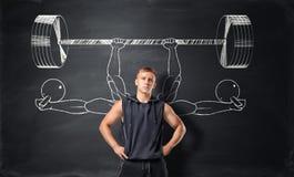 Αθλητικός αθλητικός τύπος που στέκεται στο υπόβαθρο με τα σκίτσα των barbells και των αλτήρων στοκ φωτογραφίες