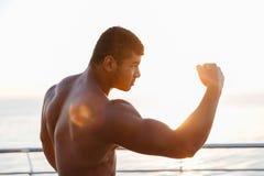 Αθλητικός αφρικανικός αθλητικός τύπος γυμνοστήθων που εκπαιδεύει υπαίθρια και που παρουσιάζει δικέφαλους μυς Στοκ Εικόνες