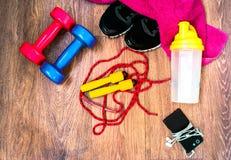 Αθλητικός εξοπλισμός στο ξύλινο πάτωμα με τα πάνινα παπούτσια, τηλέφωνο Στοκ εικόνα με δικαίωμα ελεύθερης χρήσης