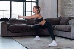 Αθλητικός καυκάσιος θηλυκός αθλητής στο μαύρο αθλητικό στηθόδεσμο και περικνημίδες που κάνουν τη δευτερεύουσα κοντόχοντρη άσκηση  στοκ εικόνες με δικαίωμα ελεύθερης χρήσης