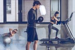 Αθλητικός νέος αθλητικός τύπος που ασκεί με τον αλτήρα στη γυμναστική Στοκ Εικόνες