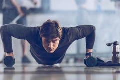 Αθλητικός νέος αθλητικός τύπος που κάνει την ώθηση UPS με τους αλτήρες στη γυμναστική Στοκ εικόνες με δικαίωμα ελεύθερης χρήσης