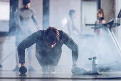 Αθλητικός νέος αθλητικός τύπος που κάνει την ώθηση UPS με τους αλτήρες στη γυμναστική Στοκ φωτογραφίες με δικαίωμα ελεύθερης χρήσης