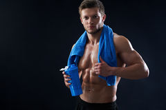 Αθλητικός νεαρός άνδρας γυμνοστήθων με μια πετσέτα και ένα μπουκάλι νερό κατόπιν Στοκ εικόνες με δικαίωμα ελεύθερης χρήσης