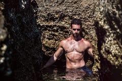 Αθλητικός νεαρός άνδρας στη θάλασσα ή ωκεανός από τους βράχους Στοκ Εικόνες