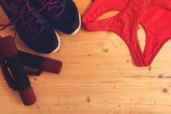 Αθλητικός στηθόδεσμος, πάνινα παπούτσια και βάρη, τοπ άποψη στοκ φωτογραφία