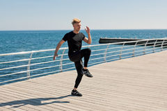 Αθλητικός τύπος που ασκεί στην αποβάθρα στην ηλιόλουστη ημέρα Στοκ Εικόνα