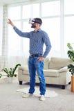 Αθλητικός τύπος που εξετάζει τα γυαλιά VR στο φωτεινό δωμάτιο Στοκ Εικόνες