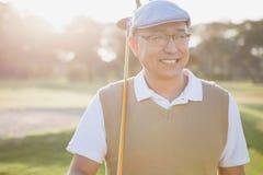 Αθλητικός τύπος που κρατά το γκολφ κλαμπ του και που κοιτάζει μακριά Στοκ Εικόνες