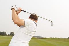 Αθλητικός τύπος που παίζει ένα παιχνίδι του γκολφ Στοκ Φωτογραφία