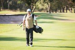 Αθλητικός τύπος που περπατά με την τσάντα γκολφ του Στοκ Φωτογραφία