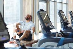 Αθλητικός τύπος που στηρίζεται στον ήλιο από το παράθυρο στη γυμναστική Στοκ Εικόνες