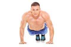 Αθλητικό άτομο που κάνει pushups και που εξετάζει τη κάμερα Στοκ Εικόνα