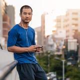 Αθλητικό ασιατικό άτομο που ακούει τη μουσική πριν από ένα τρέξιμο πόλεων Στοκ Εικόνες