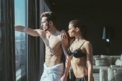 Αθλητικό ερωτευμένο κοίταγμα ζευγών έξω μέσω του παραθύρου του α Στοκ Φωτογραφία