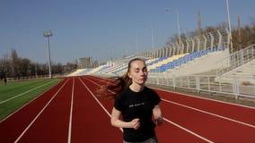 Αθλητικό ελκυστικό κατάλληλο νέο τρέχοντας γυναικών στο σε αργή κίνηση, υπαίθριο μεγάλο στάδιο workout την ηλιόλουστη ημέρα άνοιξ απόθεμα βίντεο