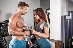 Αθλητικό κατάλληλο ζεύγος στη γυμναστική εργασία ανά τα ζευγάρια με τους αλτήρες στοκ φωτογραφία με δικαίωμα ελεύθερης χρήσης
