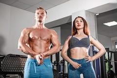 Αθλητικό κατάλληλο ζεύγος στη γυμναστική εργασία ανά τα ζευγάρια με τους αλτήρες στοκ εικόνα