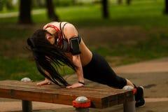 Αθλητικό κορίτσι που φορά το smartphone armband και που εκπαιδεύει με τα ακουστικά Στοκ φωτογραφία με δικαίωμα ελεύθερης χρήσης