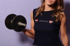 Αθλητικό κορίτσι σε έναν μαύρο αλτήρα εκμετάλλευσης πουκάμισων στοκ εικόνες