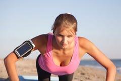 Αθλητικό κορίτσι ώθηση-UPS στην παραλία Στοκ Φωτογραφία