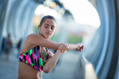Αθλητικό νέο τέντωμα γυναικών πριν από την άσκηση ακούοντας τη μουσική Στοκ Φωτογραφία