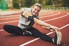 Αθλητικό νέο τέντωμα γυναικών στον τομέα διαδρομής Στοκ Εικόνες