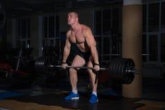 Αθλητικό υπόβαθρο Νέος αθλητής που παίρνει έτοιμος για την κατάρτιση ανύψωσης βάρους Στοκ Φωτογραφίες