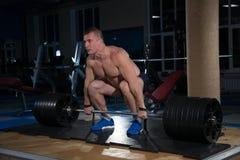 Αθλητικό υπόβαθρο Νέος αθλητής που παίρνει έτοιμος για την κατάρτιση ανύψωσης βάρους Στοκ Εικόνες