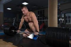 Αθλητικό υπόβαθρο Νέος αθλητής που παίρνει έτοιμος για την κατάρτιση ανύψωσης βάρους Στοκ Φωτογραφία