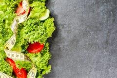 αθλητισμός σιτηρεσίου Λαχανικά Αγγούρι, ντομάτες, σαλάτα στο σκοτεινό υπόβαθρο πετρών Στοκ Εικόνα