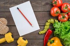 αθλητισμός σιτηρεσίου Λαχανικά, αλτήρες και εκατοστόμετρο Πιπέρια, ντομάτες, σαλάτα στο αγροτικό υπόβαθρο Στοκ Εικόνα