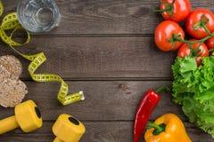 αθλητισμός σιτηρεσίου Λαχανικά, αλτήρες και εκατοστόμετρο Πιπέρια, ντομάτες, σαλάτα στο αγροτικό υπόβαθρο Στοκ Εικόνες