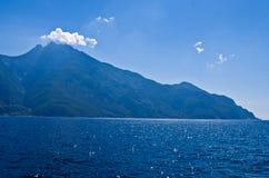 Αιγαίο πέλαγος, σκιαγραφία των ιερών βουνών Athos και ένα μικρό σύννεφο επάνω από την κορυφή βουνών Στοκ Εικόνες