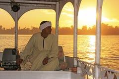Αιγυπτιακός καπετάνιος που οδηγεί τη βάρκα του στον ποταμό του Νείλου στο ηλιοβασίλεμα, Λ Στοκ Φωτογραφίες
