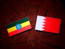 Αιθιοπική σημαία με την του Μπαχρέιν σημαία σε ένα κολόβωμα δέντρων Στοκ Φωτογραφία
