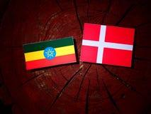 Αιθιοπική σημαία με τη δανική σημαία σε ένα κολόβωμα δέντρων που απομονώνεται Στοκ εικόνα με δικαίωμα ελεύθερης χρήσης