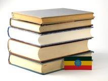Αιθιοπική σημαία με το σωρό των βιβλίων στο άσπρο υπόβαθρο Στοκ εικόνα με δικαίωμα ελεύθερης χρήσης